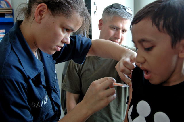 US Navy (USN) Hospitalman (HN) Shannon Dawkins inoculates a boy at the Peukan Bada Health Clinic, Banda Aceh, Indonesia, as part of the US Military Sealift Command (MSC) Mercy Class Hospital Ship USNS MERCY (T-AH 19), humanitarian assistance program, on Jul. 25, 2006. The MERCY is on a five-month humanitarian assistance deployment.(U.S. Navy official photo by Mass Communication SPECIALIST SEAMAN Joseph Caballero) (Released)