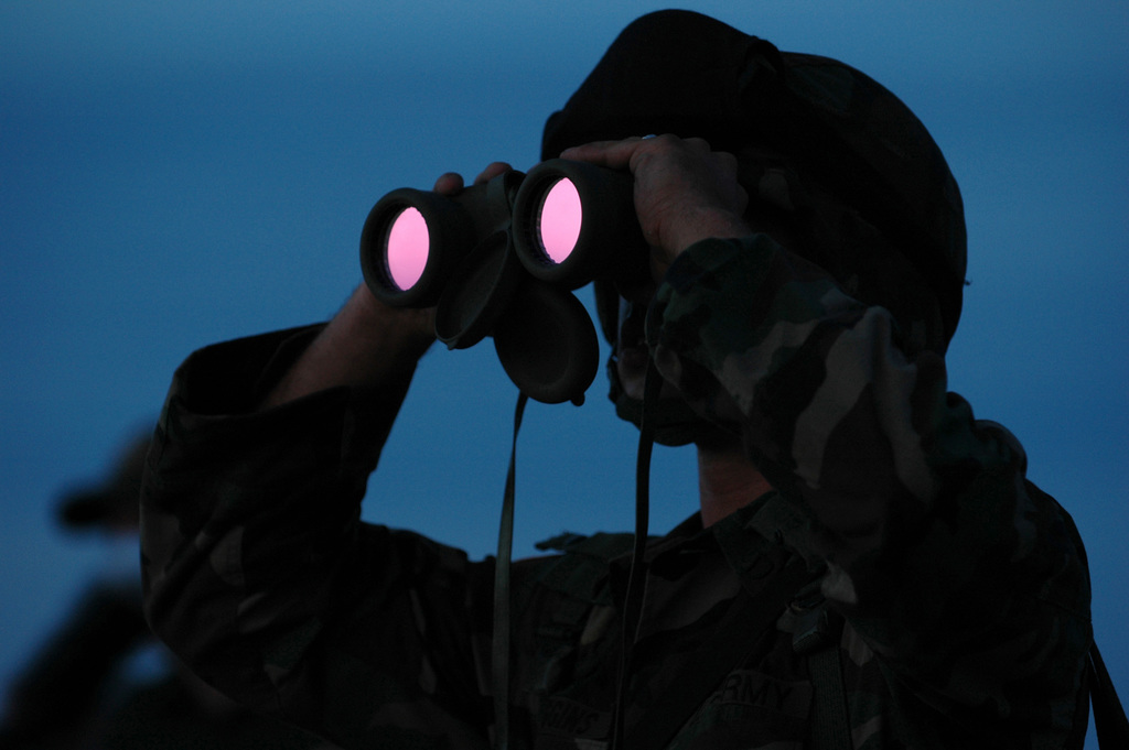 North Carolina Army National Guard (NCARNG) Private First Class (PFC) Holt Duggins, 252nd Combined Arms Battalion (CAB), Fayetteville, North Carolina (NC), looks through his binoculars at an area of the Mexican border in San Luis, Arizona (AZ). National Guard Soldiers are working with the US Border Patrol in support of Operation JUMP START
