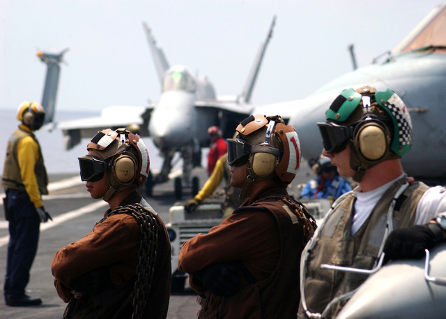 US Navy (USN) plane captains observe flight operations, prior to the launch of a F/A-18C Hornet fighter/attack aircraft, on the USN Nimitz Class Aircraft Carrier USS THEODORE ROOSEVELT (CVN 71), which is in the Atlantic Ocean (AOC) in support of the Fleet Response Plan (FRP)