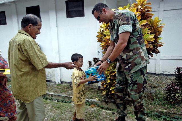 US Navy (USN) MASTER At Arms Second Class (MA2) Ernest Lopez, US Military Sealift Command (MSC) Mercy Class Hospital Ship USNS MERCY (T-AH 19), gives a child a skateboard helmet outside the Kesdam Military Hospital, Banda Aceh, Indonesia, as part of a humanitarian assistance program, on Jul. 27, 2006.(U.S. Navy official photo by Mass Communication SPECIALIST SEAMAN Apprentice Mike Leporati) (Released)