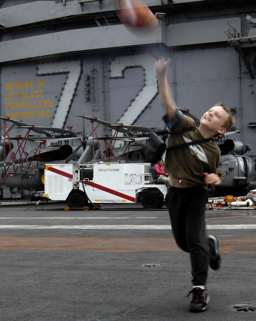 Luke Ward, a US Navy (USN) child plays football during a steel beach picnic on the flight deck of the USN Nimitz Class Aircraft Carrier USS ABRAHAM LINCOLN (CVN 72) during a Tiger Cruise in the Pacific Ocean. Tiger Cruise is provided for family members and friends of the crew to give them an opportunity to experience life at sea for a week