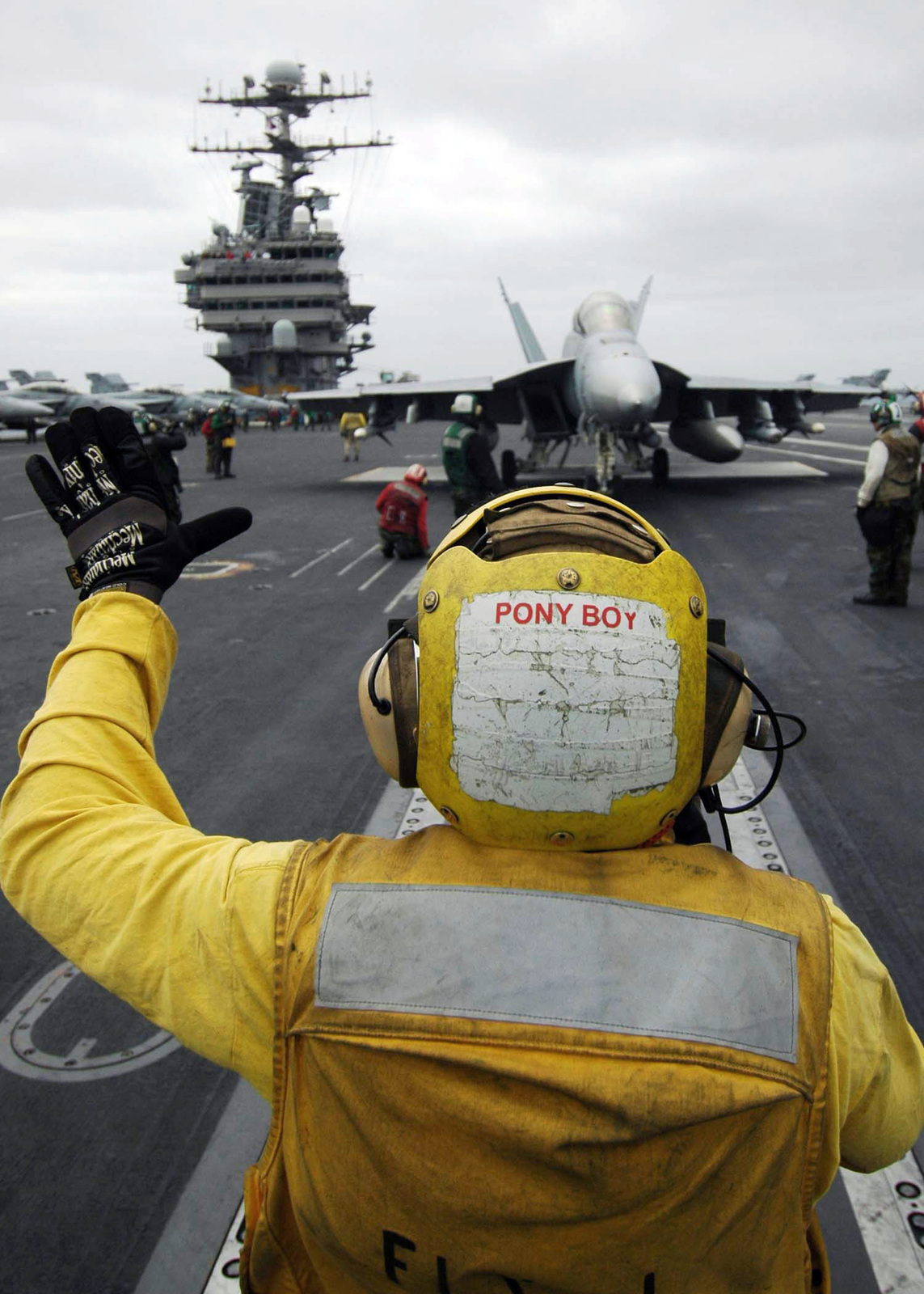 US Navy (USN) Aviation Boatswain's Mates Handlers direct a USN F/A-18F Super Hornet assigned to the USN Strike Fighter Squadron 2 (VFA-2) during operations on the flight deck of the USN Nimitz Class Aircraft Carrier USS ABRAHAM LINCOLN (CVN 72). The LINCOLN and USN Carrier Air Wing 2 (CVW-2) are completing a deployment in the Pacific Ocean