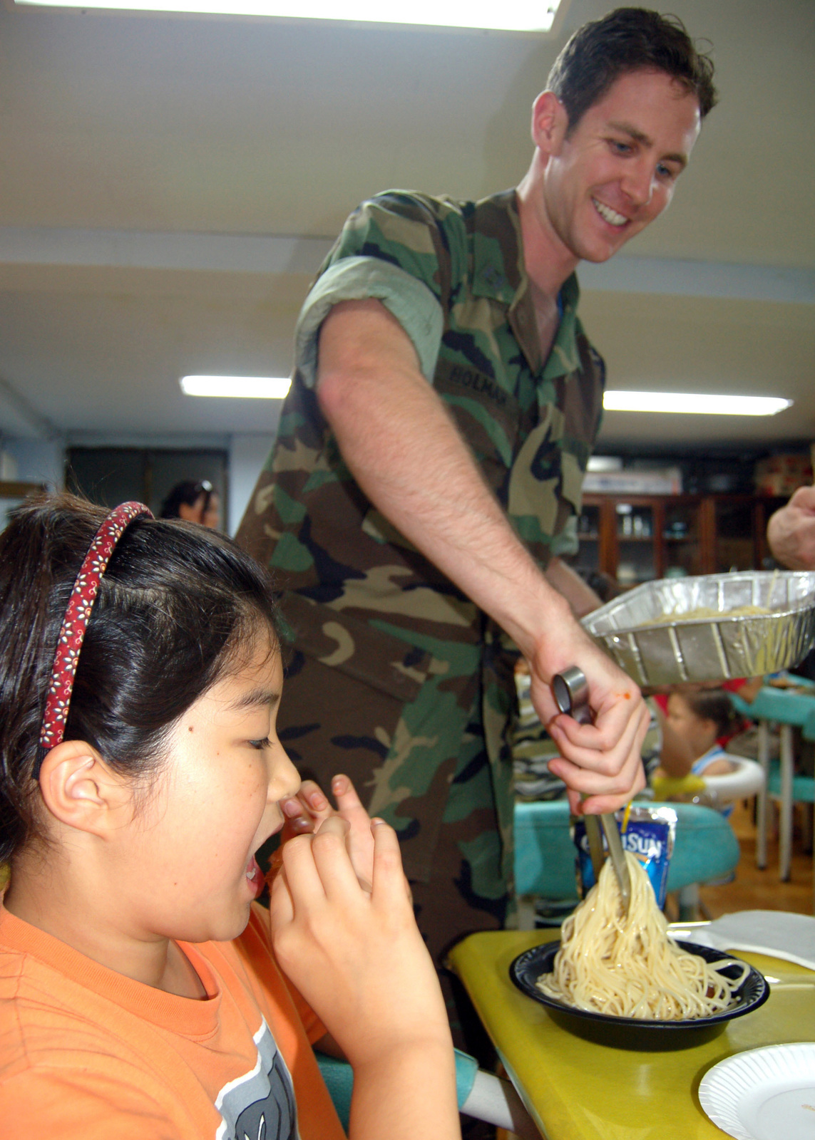 060810-N-4208W-002 (Aug. 10, 2006)US Navy (USN) LT. Sean Holman, from Commander Naval Forces Korea (CNFK), serves dinner to children at Hye-shim Won Orphanage in Seoul, Korea (KOR). The event is part of a monthly birthday party that CNFK Sailors host for the orphanage.U.S. Navy official photo by Mass Communication SPECIALIST 1ST Class Lisa Wassilieff (RELEASED)