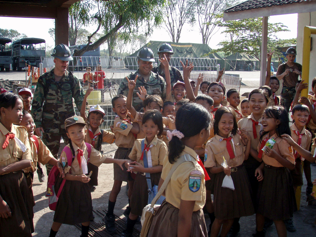 (From right-to-left), U.S. Navy Hospital Corpsman 1ST Class Scott Gervasi, Builder 2nd Class Gianfranco Bravo and Ship's Serviceman 2nd Class Antwon Washington, all assigned to Naval Mobile Construction Battalion 1, look on as school children wave for photographs during Exercise Cooperation Afloat Readiness and Training (CARAT) in Indonesia on Aug. 10, 2006. The USN Seabees joined a group of Indonesian Marines in several renovation projects, which included placing tiles at a village schoolhouse. CARAT is an annual series of bilateral maritime exercises between the U.S. and Southeast Asia nations designed to build relationships and enhance the operational readiness of the participating...
