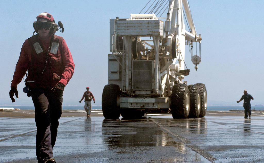 """060815-N-7130B-165 (Aug. 15, 2006)US Navy (USN) Sailors from the Air Department's Crash and Salvage Division move the aircraft crash crane""""Tilly""""in preparation for testing the countermeasure wash down system on the flight deck of USN Nimitz Class Aircraft Carrier USS RONALD REAGAN (CVN 76). The REAGAN is currently conducting routine carrier operations in the Pacific Ocean (POC).U.S. Navy official photo by Mass Communication SPECIALIST 2nd Class (AW/SW) Aaron Burden (RELEASED)"""