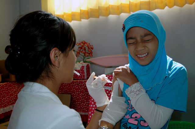 Chanda Plong, a Project HOPE Nurse assigned to the U.S. Military Sealift Command, Mercy Class Hospital Ship USNS MERCY (T-AH 19), gives an immunization to a patient at the RSUD Tarakan Hospital, during a humanitarian and civic deployment to Tarakan, Indonesia on Aug. 16, 2006.(U.S. Navy photo by Mass Communication SPECIALIST SEAMAN Joseph Caballero) (Released)