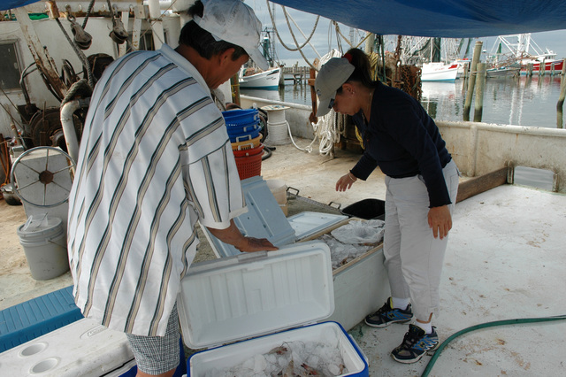 [Hurricane Katrina] Pass Christian, Miss., August 16, 2006 -- Danh Khoung (left) and Nga Dang work on their shrimp boat using the rebuilt Pass Christian marina as their base of operations.  Mark Wolfe/FEMA