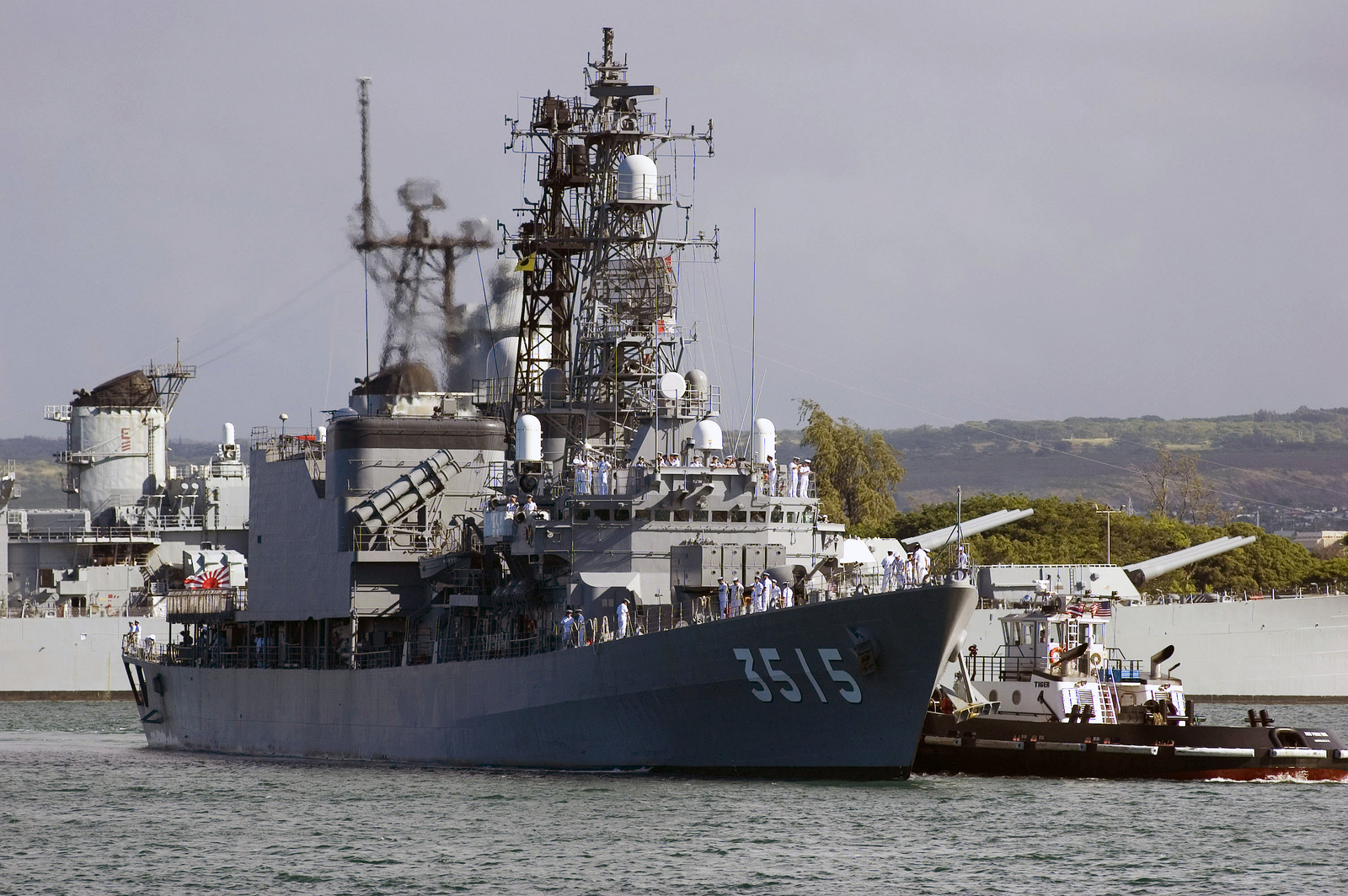 The Japanese Maritime Self Defense Force JDS YAMAGIRI (TV 3515) is assisted by a tugboat as it passes the USS MISSOURI Memorial at Naval Station Pearl Harbor, Hawaii, on Aug. 18, 2006. More than 1,000 Japanese Sailors are visiting Pearl Harbor during a worldwide training and international relations cruise. (U.S. Navy photo by Mass Communications SPECIALIST 1ST Class Dennis C. Cantrell) (Released)