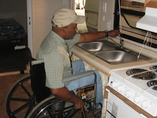 [Hurricane Katrina/Hurricane Rita] Baton Rouge, La., August 19, 2006 - FEMA employee Vince Prevot demonstrates the features of the new trailers being assigned to disabled evacuees. The trailers are ADA compliant and feature electric heat, a shower with a built-in seat an other elements designed to make life easier for those confined to chairs. Keith Riggs/FEMA.