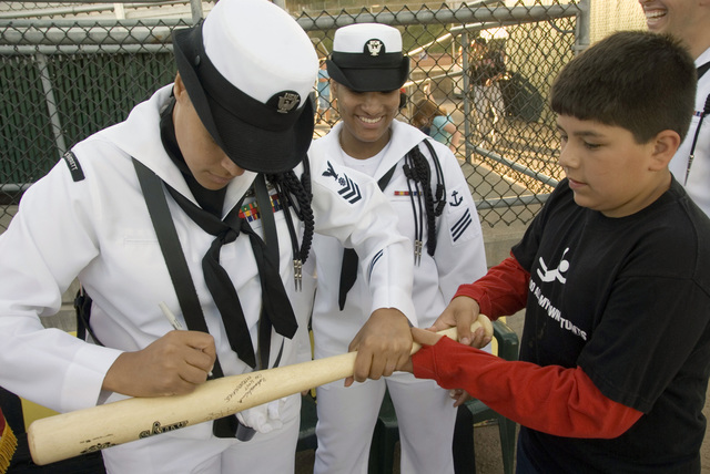U.S. Navy Quarter MASTER 1ST Class Johnnie Hong, from Naval Station Everett, Wash., signs a bat for a fan prior to the start of an Everett Aqua Sox baseball game during Military Appreciation Night at Memorial Stadium in Everett on Aug. 19, 2006. The Aqua Sox, a single-A professional baseball team affiliated with the Major League Baseball (MLB) Seattle Mariners, showed their support for America's service members by hosting Military Appreciation Night here. (U.S. Navy photo by Mass Communication SPECIALIST 3rd Class Douglas G. Morrison) (Released)