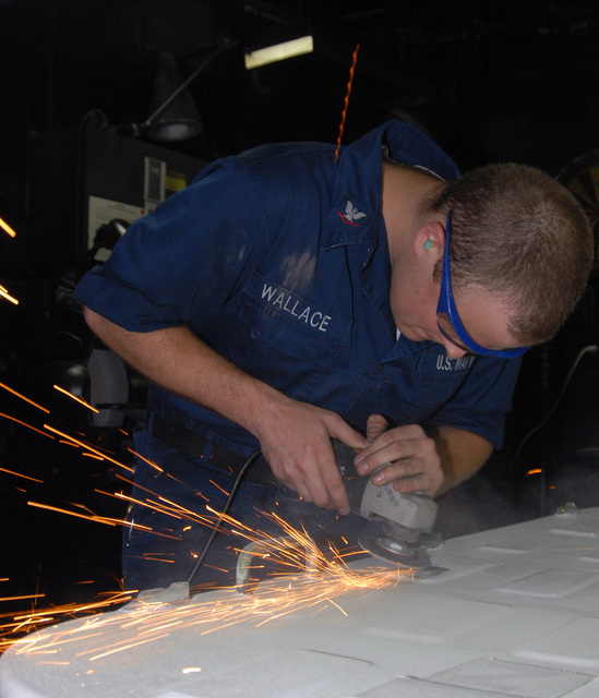U.S. Navy PETTY Officer 3rd Class Wesley R. Wallace Class, Hull Technician, grinds a hatch for a cypher lock installation aboard the Wasp Class Amphibious Assault Ship USS IWO JIMA (LHD 7) on Aug. 21, 2006. The IWO JIMA is deployed to the Red Sea in support of Maritime Security Operations.  (U.S. Navy photo by Mass Communication SPECIALIST SEAMAN Christopher L. Clark) (Released)