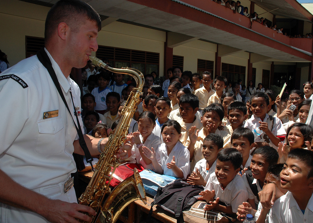 U.S. Navy Musician 1ST Class Ian Charleton (left), U.S. Navy Show Band saxophonist embarked with the Medical Treatment Facility aboard the U.S. Navy Military Sealift Command Mercy Class Hospital Ship USNS MERCY (T-AH 19), plays a saxophone solo for young Indonesian students, during a performance at a local Catholic school in Kupang, East Nusa Tenggara Province (West Timor), Indonesia, on Aug. 23, 2006. The MERCY is in the fourth month of a five-month humanitarian and civic assistance deployment to Southeast Asia. (U.S. Navy photo by Mass Communication SPECIALIST 1ST Class Michael R. McCormick) (RELEASED)