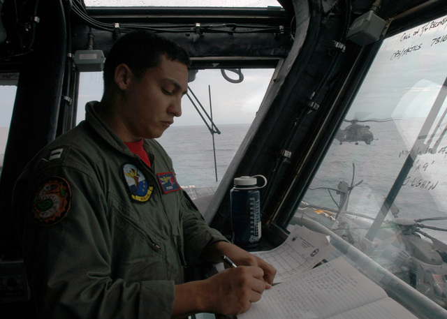 U.S. Navy LT. Dantel Morreira, Helicopter Mine Countermeasure Squadron 14 (HM-14), makes a log entry as an MH-53E Sea Dragon helicopter lifts off from the Wasp Class Amphibious Assault Ship USS KEARSARGE (LHD 3) on Aug. 26, 2006.  The KEARSARGE is particpating in PANAMAX 2006, a multi-national exercise tailored to the defense of the Panama Canal.(U.S. Navy photo by Mass Communication SPECIALIST SEAMAN Christopher Newsome) (Released)