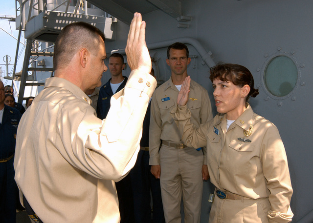 US Navy Command MASTER CHIEF (SW) John G. Becker II administers the oath of enlistment to CHIEF MASTER-at-Arms (SW) Mary C. McQuain during her re-enlistment ceremony aboard the Amphibious Command Ship USS BLUE RIDGE (LCC 19). BLUE RIDGE is currently deployed in Southeast Asia supporting Exercise Ulchi Focus Lens and the 7th Fleet's interoperability and training commitments in maritime operations. (U.S. Navy photo by Mass Communications SPECIALIST 3rd Class Tucker M. Yates) (Released)