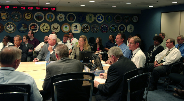 Washington, DC, August 29, 2006 -- FEMA officials, including R. David Paulison the FEMA Director (table head, blue shirt), Vice Admiral Harvey Johnson, Deputy Director (white shirt, to left of Paulison) and other FEMA employees gather in the NRCC (National Response and Coordination Center) conference room where they receive a (VTC) Video Teleconferece briefing on the preperations for the landfall of tropical storm Ernesto in Florida.  FEMA/Bill Koplitz