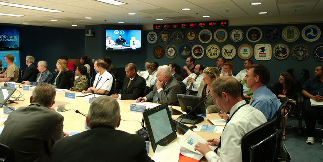 Washington, DC, August 30, 2006 -- FEMA officials, including R. David Paulison the FEMA Director (table head, blue shirt), Vice Admiral Harvey Johnson, Deputy Director (white shirt, to left of Paulison) and other FEMA employees gather in the NRCC (National Response and Coordination Center) conference room where they receive a (VTC) Video Teleconferece briefing on the preperations for the landfall of tropical storm Ernesto in Florida.  FEMA/Bill Koplitz
