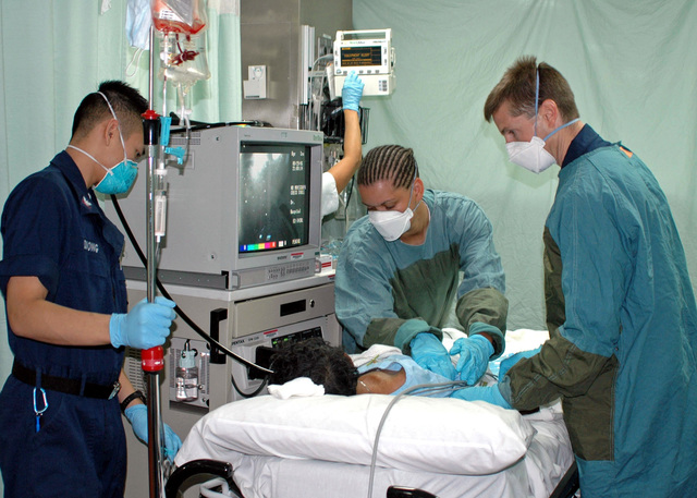 U.S. Navy LT. CMDR. Todd Sheer (right), PETTY Officer 3rd Class Bryan Duong (left, Hospital Corpsman 3rd Class, and SEAMAN Shannon Dawkins (center), Hospitalman prepare to perform an endoscopies on a patient aboard the U.S. Navy Military Sealift Command Hospital Ship, the USNS MERCY (T-AH 19). The USNS MERCY (T-AH 19) which is anchored off the coast of Dili, East Timor provides humanitarian assistance to local residents. Aug. 30, 2006. (U.S. Navy photo by CHIEF Mass Communication SPECIALIST Don Bray) (Released)