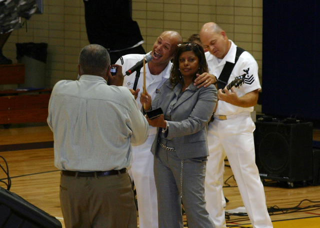 """U.S. Navy Musician 3rd Class Spencer Hassenritter, assigned to Navy Band Mid-South rock ensemble""""Freedom,""""poses for the camera while performing alongside Warrensville Heights High School Assistant Principal Debra Cambell during Navy Week at Cleveland, Ohio, on Aug. 30, 2006. The Cleveland Navy Week, which runs from Aug. 28-Sept. 4, 2006, features Navy participation in community events ranging from professional baseball and football games to the Cleveland National Air Show. (U.S. Navy photo by Mass Communication SPECIALIST 2nd Class Michael Sheehan) (Released)"""