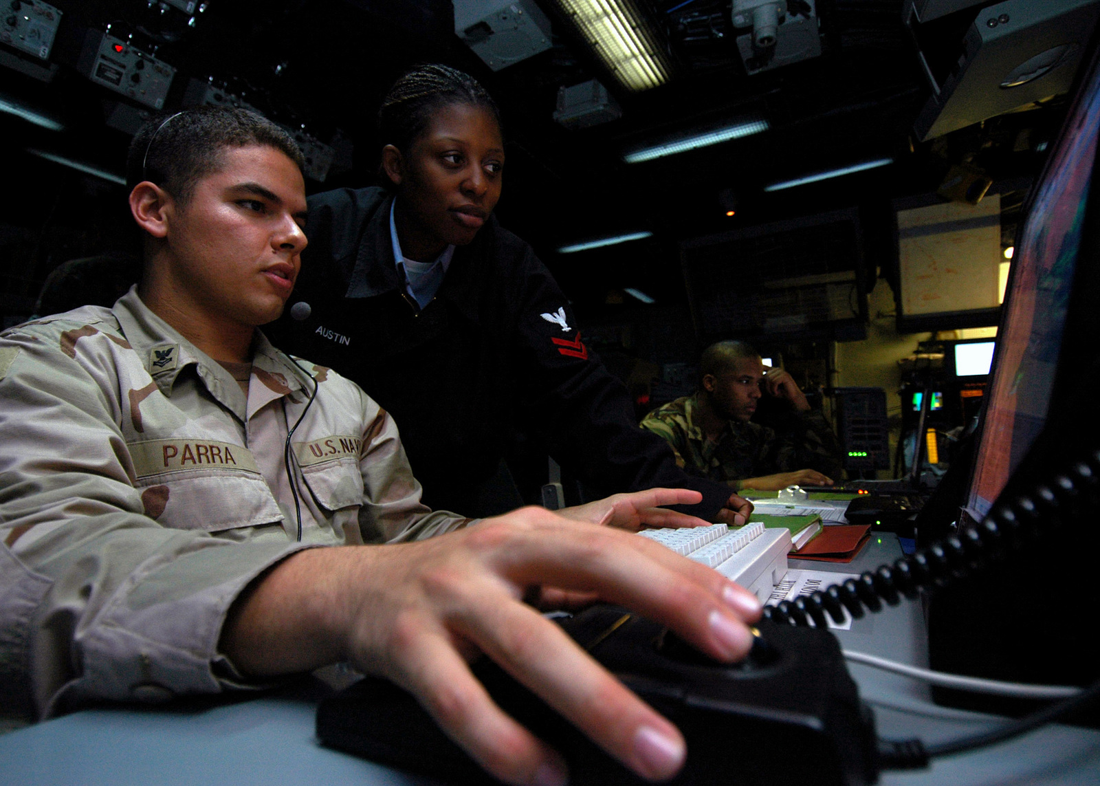 U.S. Navy PETTY Officer 2nd Class Miguel Parra, and PETTY Officer 2nd Class Tina Austin, Air Traffic Controllers, Tactical Air Control Squadron 22 (TACRON-22), man the Tactical Air Control Center aboard the Wasp Class Amphibious Assault Ship USS IWO JIMA (LHD 7) on Aug. 30, 2006. The IWO JIMA is on a six-month deployment to the Gulf of Aden in support of Maritime Security Operations and the Global War on Terrorism.(U.S. Navy photo by Mass Communication SPECIALIST Joshua T. Rodriguez) (Released)