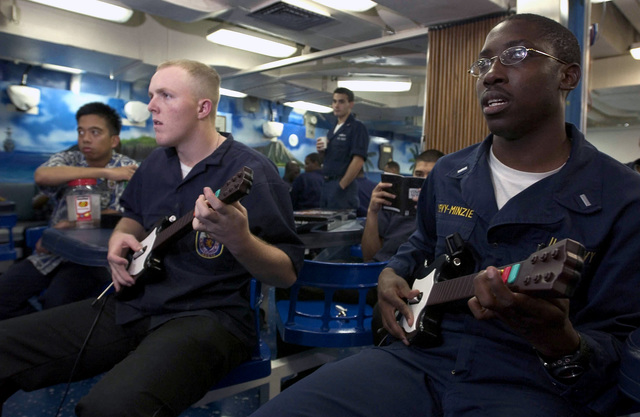 "U.S. Navy Culinary SPECIALIST SEAMAN Damien McCullough, (left), and LT. j.g. Levy-Minzie, play an electric guitar video game during""game night"", aboard the Arleigh Burke Class Guided Missile Destroyer USS HOPPER (DDG 70) on Sep. 2, 2006. The HOPPER is on a scheduled deployment in support of Maritime Security Operations and the Global War On Terrorism.(U.S. Navy photo by Mass Communication SPECIALIST Second Class John L. Beeman) (Released)"