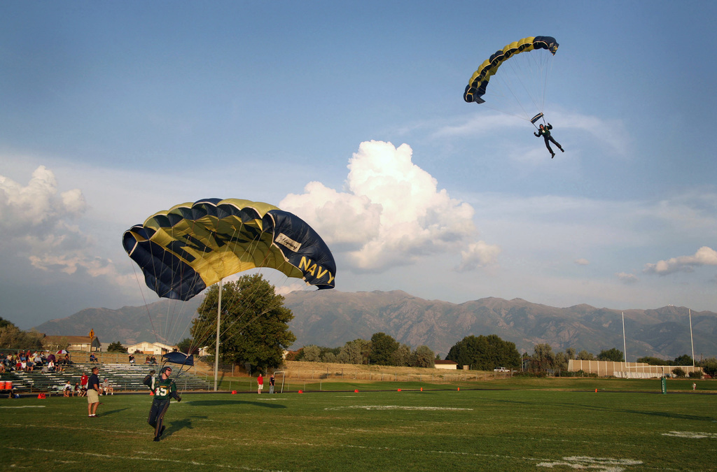 """Members of the U.S. Navy Parachute Demonstration Team""""Leap Frogs""""land at the football field at Clearfield High School, Clearfield, Utah, prior to the school's season opener on Sept. 8, 2006. The demonstration was part of Utah Navy Week festivities, a 10-day series of more than 160 events designed to raise awareness of the Navy and enhance recruiting efforts in the region. (U.S. Navy photo by CHIEF Mass Communication SPECIALIST Gary Ward) (Released)"""