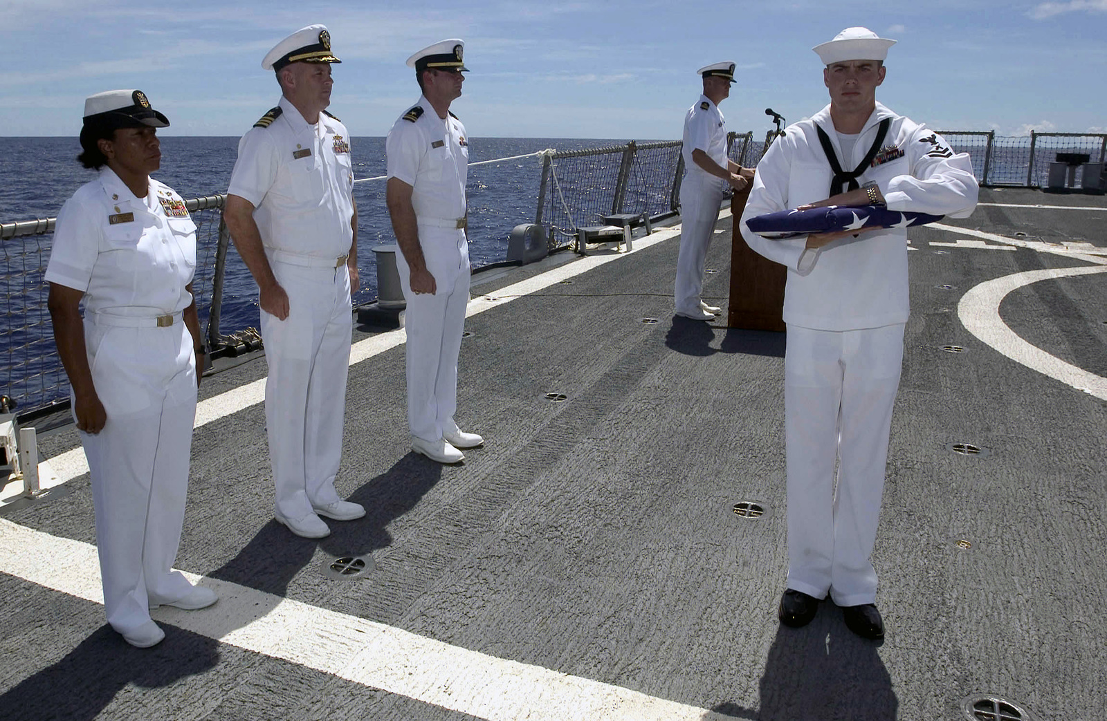 U.S. Navy GUNNER's Mate Second Class Robert Prine secures the folded American Flag, as CMDR. Peter Driscoll, Commanding Officer, Arleigh Burke Class Guided Missile Destroyer USS HOPPER (DDG 70), speaks during a Burial at Sea for retired CHIEF Warrant Officer Charles Paris, Sep. 8, 2006.(U.S. Navy photo by Mass Communication SPECIALIST Second Class John L. Beeman) (Released)