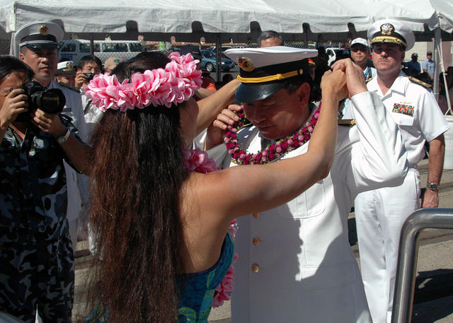Chinese Peoples Liberation Army Navy Rear Adm. Wang Fushan, Deputy Commander, North Sea Fleet, receives a lei from a Polynesian dancer before departing Naval Station Pearl Harbor, Hawaii, on Sept. 10, 2006. Chinese Sailors from two ships, the Luhu (Type 052) Class Guided Missile Destroyer QINGDAO (DDG 113) and the Fuquing Class Replenishment Ship HONGZEHU (AOR 881), spent three days at NS Pearl Harbor during a Goodwill Visit. (U.S. Navy photo by Mass Communication SPECIALIST 1ST Class James E. Foehl) (Released) )
