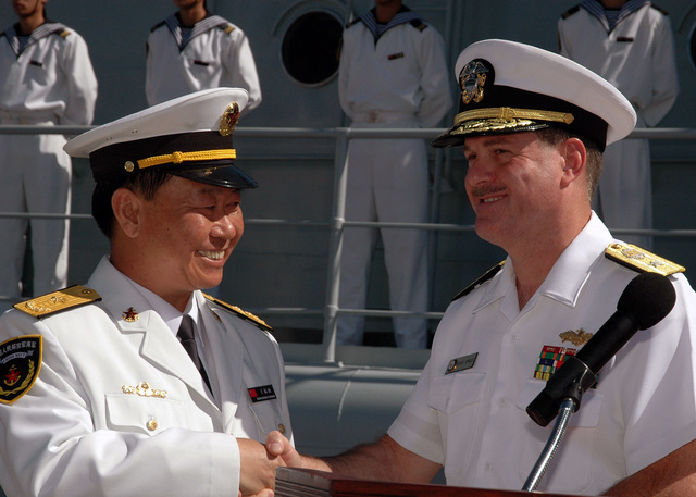U.S. Navy Rear Adm. Gary A Engle (right), Commander, Pacific Division, Naval Facilities Engineering Command, shakes hands with Chinese Peoples Liberation Army Navy Rear Adm. Wang Fushan, Deputy Commander, North Sea Fleet, during the PLA Navy departure ceremony on Sept. 10, 2006 at Naval Station Pearl Harbor, Hawaii. During their three-day Goodwill Visit, Chinese Sailors from the Luhu (Type 052) Class Guided Missile Destroyer QINGDAO (DDG 113) and the Fuquing Class Replenishment Ship HONGZEHU (AOR 881) interacted with their U.S. Navy counterparts and they also experienced the unique culture of Hawaii. (U.S. Navy photo by Mass Communication SPECIALIST 1ST Class James E. Foehl) (Released)
