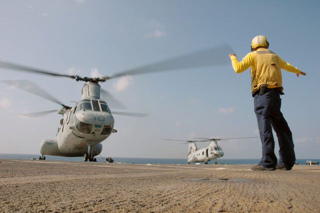 A U.S. Navy Landing Signal Enlisted, holds a U.S. Marine CH-46 Sea Knight aboard the Harpers Ferry Class Dock Landing Ship USS HARPERS FERRY (LSD 49), during deck landing qualifications on Sep. 24, 2006. The HARPERS FERRY is currently embarked on its fall patrol.U.S. Navy photo by Mass Communication SPECIALIST Second Class Brian P. Biller (Released)