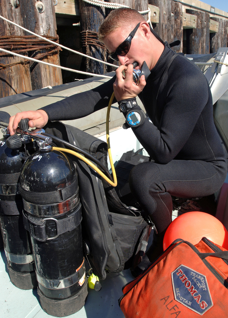 """U.S. y Steel Worker 3rd Class (DV) Jesse Hamblin, from Underwater Construction Team 1, inspects his oxygen tank before a dive at al Station Norfolk, Va., on Oct. 2, 2006. He and other Sailors assisted in the delivery of the replica ship DISCOVERY to the Royal Fleet Auxiliary Ship RFA FORT ROSALIE (A385). DISCOVERY is being transported to the United Kingdom where it will be the center-piece of a major tour promoting the 400th anniversary of the settlement in Jamestown, Va. A""""fly-boat""""of the British East India Company, DISCOVERY was the smallest of three ships that took part in the voyage from London to the new colony of Virginia, leading to the founding of Jamestown in 1607. (U.S...."""