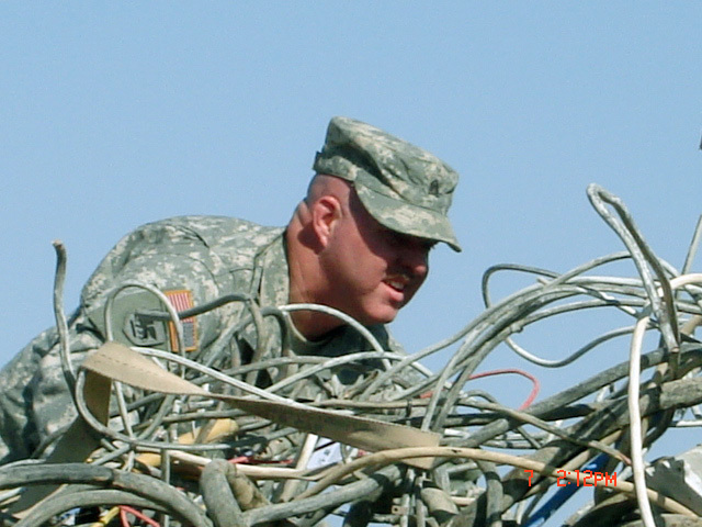 U.S. Army SGT. Theodore Miller assigned to Charlie Company, 449th Aviation Support Battalion, Texas Army National Guard, sorts through various types of wires at the Defense Reutilization and Marketing Office site, to find the correct wire in order to improve his Joint Node Network (JNN) operation at Logistic Support Area, Anaconda, Balad Air Base, Iraq, on Oct. 7, 2006, during Operation Iraqi Freedom. (A3606) (U.S. Army PHOTO by SPC. Kaleena Calderas) (Released)