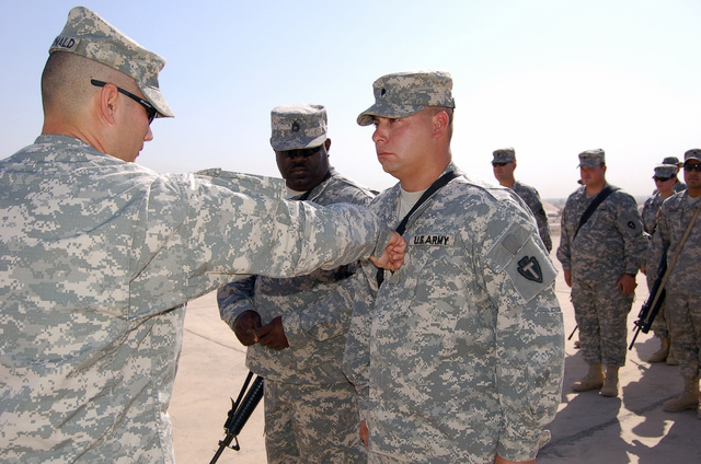 U.S. Army SGT.  Nickolas Tello, right, receives his promotion from 1ST LT. Michael McDonald, left, while SGT. 1ST Class Tony Boneparte looks on during operation Iraqi Freedom at Logistic Support Area (LSA) Anaconda, Balad Air Base, Iraq, on Oct. 9, 2006. The Guardsmen are all members of the the Texas Army National Guard (TXARNG) Headquarters and Services Company, 449th Aviation Support Battalion. (A3606) (U.S. Army photo by SGT. Huey Kehl) (Released)