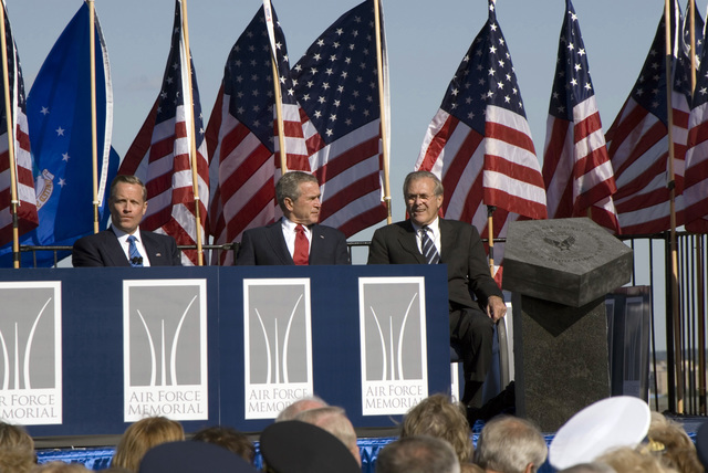 The Honorable George W. Bush (center), President of the United States, and The Honorable Donald H. Rumsfeld (right), U.S. Secretary of Defense, talk together, as Mr. Ross Perot, Jr. (left), Chairman of the Air Force Memorial Foundation, looks at the audience, during the dedication ceremony of the Air Force Memorial at its Arlington, Va., location, overlooking the Pentagon, on Oct. 14, 2006. (DoD photo by MASTER SGT. Sean M. Brennan) (Released)