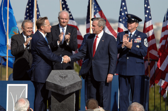 The Honorable George W. Bush (front, right), President of the United States, accepts the Air Force Memorial on behalf of all American citizens from Mr. Ross Perot, Jr. (front, left), Chairman of the Air Force Memorial Foundation, during the dedication ceremony at its Arlington, Va., location, overlooking the Pentagon, on Oct. 14, 2006. Looking on and applauding are (left to right): the Honorable Donald H. Rumsfeld, U.S. Secretary of Defense, the Honorable Michael W. Wynne, Secretary of the Air Force, U.S. Air Force GEN. T. Michael Moseley (immediately behind President Bush), Air Force CHIEF of STAFF, and CHIEF master SGT. Of the Air Force Rodney J. McKinley. (U.S. Air Force photo by...