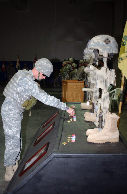 U.S. Army SGT. MAJ. Jerry Taylor, the SGT. MAJ. of 25th Infantry Division (ID), places a coin on the table with Kevlar helmets mounted on top of M16 rifles in honor of the memory of STAFF SGT. Ryan Eugene Haupt, SGT. Norman Robert Taylor III and SPC. Nathan Joseph Frigo, all with Headquarters and Headquarters Company and attached to Attack Company, 1-68 Combined Arms Battalion. The memorial ceremony is at Forward Operating Base Warhorse, Iraq. (U.S. Army PHOTO by SPC. Elisha Dawkins) (Released)
