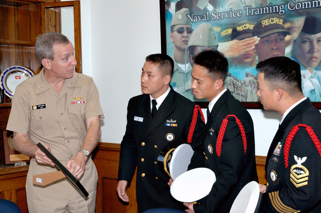 U.S. Navy Rear Adm. Gary R. Jones (left), Commander of the Naval Service Training Command, shows his office keepsakes to CHIEF Quartermaster ManSuk Woo and Kichun Nam, drill instructors with the Korean Navy, following an exchange visit to Recruit Training Command, Great Lakes, Ill., as CHIEF Quartermaster Kichun Nam, a recruit division Commander at Recruit Training Command, served as translator during the visit. (U.S. Navy PHOTO by Hospital Corpsman 1ST Class Duane Snader) (Released)