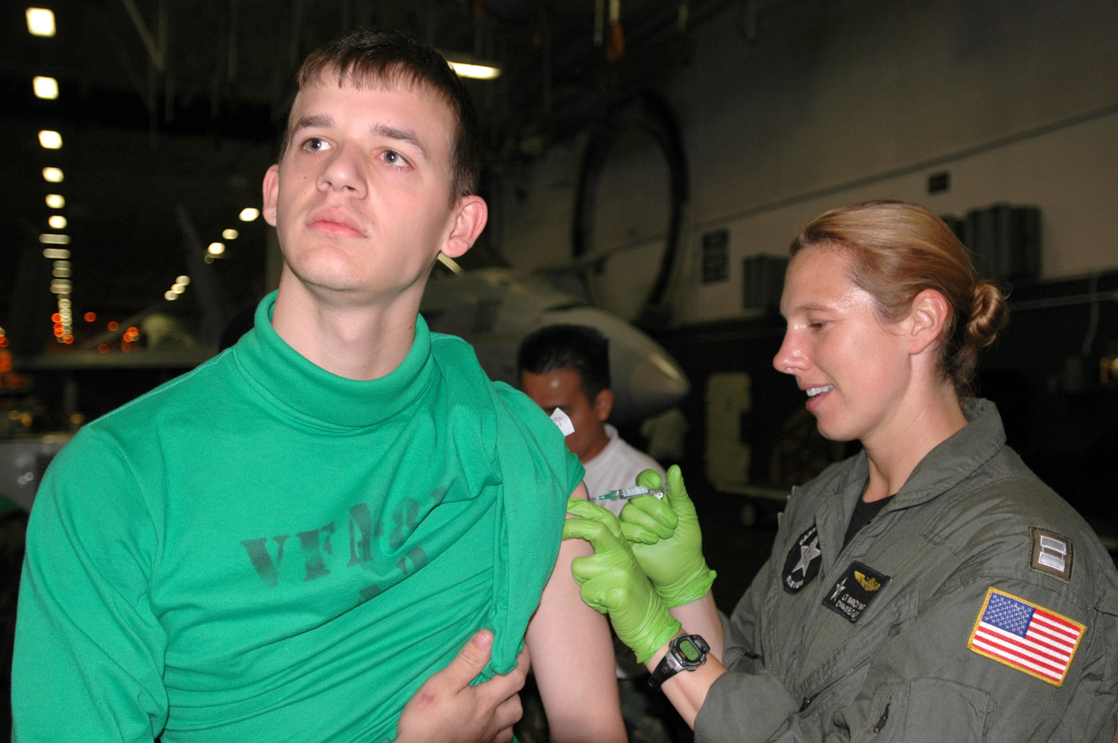 """U.S. Navy Aviation Maintenance Administrationman 3rd Class Joshua Hardin (left) assigned to the""""Sunliners""""of Strike Fighter Squadron 81, receives an Influenza vaccination from LT. Nancy Warner (right) assigned to Carrier Air Wing 11 in the hangar bay aboard the Aircraft Carrier USS NIMITZ (CVN 68) off the coast of Calif., Oct. 26, 2006. (U.S. Navy photo by Mass Communication SPECIALIST SEAMAN Gretchen Marie Roth) (Released))"""