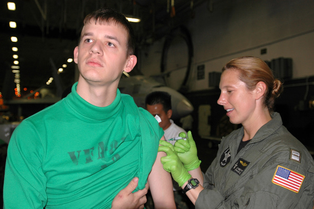 "U.S. Navy Aviation Maintenance Administrationman 3rd Class Joshua Hardin (left) assigned to the""Sunliners""of Strike Fighter Squadron 81, receives an Influenza vaccination from LT. Nancy Warner (right) assigned to Carrier Air Wing 11 in the hangar bay aboard the Aircraft Carrier USS NIMITZ (CVN 68) off the coast of Calif., Oct. 26, 2006. (U.S. Navy photo by Mass Communication SPECIALIST SEAMAN Gretchen Marie Roth) (Released))"