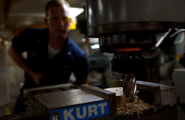U.S. Navy Machinery Repairman 3rd Class Kevin Weeks manufactures a clasp on a universal mill in the machine shop onboard the Nimitz Class Aircraft Carrier USS RONALD REAGAN (CVN 76) on Oct. 26, 2006. The REAGAN is currently conducting training squadron carrier qualifications off the coast of Southern California. (U.S. Navy photo by Mass Communication SPECIALIST SEAMAN Benjamin Brossard) (Released)