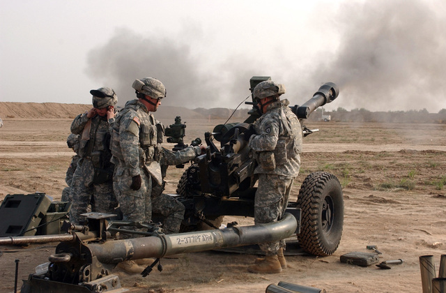 U.S. Army Canoneers with Alpha Battery, 2nd Battalion, 377th Parachute Field Artillery Regiment, fire a 105 mm Howitzer on a fire mission near Forward Operating Base Kalsu, Iraq. The Soldiers are calibrating their cannons in order to provide fire support. (U.S. Army PHOTO by SPC. Elisha Dawkins) (Released)