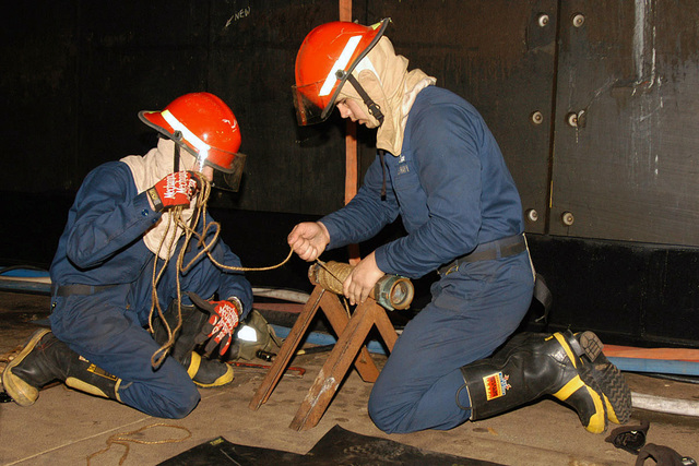 U.S. Navy Damage Controlman 3rd Class Thomas Abadie and Damage Controlman Fireman Anthony Abrao, work to obtain all the necessary gear to patch a simulated broken pipe, during a flooding drill for the Surface Line Week competition, at Norfolk, Va. (U.S. Navy PHOTO by Mass Communication SPECIALIST 2nd Class Susan Milton) (Released)
