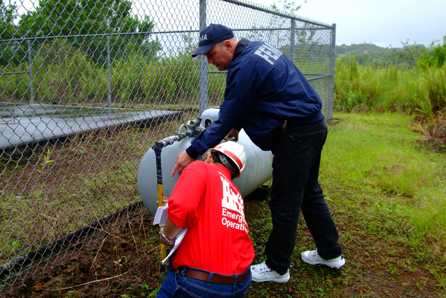 [Earthquake] Pepeekeo, HI, November 13, 2006 - FEMA Mitigation Map Mod. specialist Marshall Marik and U.S. Army Corps structural engineer Peter Lam inspect a gas line that provides energy to operate a police/fire communication tower. The FEMA coordinated mitigation inspection team was checking for a rupture in the line that may exist after a recent series of earthquakes. Adam DuBrowa/FEMA.