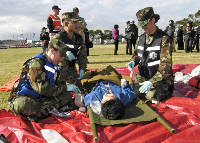 U.S. Navy Doctors and Hospital Corpsmen assigned to the U.S. Naval Hospital Yokosuka, Japan, Special Medical Operation Response Team (SMORT), give emergency care to a casualty during a mass casualty drill held at the Hakozaki Fuel Terminal on Azuma Island, on Nov. 15, 2006. The mass casualty drill featured real-life scenarios, enabling Japanese and American medical staff and rescue teams to receive extensive hands-on training. (U.S. Navy photo by Mass Communication SPECIALIST 2nd Class Chantel M. Clayton) (Released)