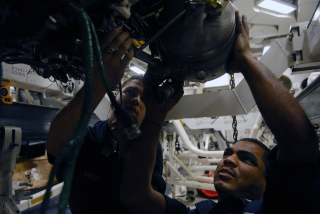 U.S. Navy Aviation Machinist's Mate 3rd Class Gowtum Mooroteea holds an oil tank in place as Aviations Machinist's Mate AIRMAN Everett Mackey tightens a bolt on a jet engine at the jet shop onboard the Nimitz Class Aircraft Carrier USS RONALD REAGAN (CVN 76) on Nov. 16, 2006. The REAGAN is currently conducting training squadron carrier qualifications off the coast of Southern California. (U.S. Navy photo by Mass Communication SPECIALIST SEAMAN (AW/SW) Kathleen Gorby) (Released)