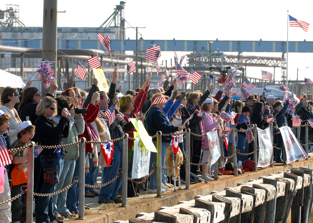 NORFOLK, Va. (Nov. 20, 2006)  Family members of the Sailors aboard Los Angeles-class nuclear-powered fast-attack submarine USS ALBANY (SSN 753) cheer and wave flags as the sub returns home from a six-month deployment. During her deployment, ALBANY participated in operations in the Atlantic Ocean and Caribbean Sea. U.S. Navy photo by Mass Communication SPECIALIST SEAMAN Kelvin Edwards (Released)