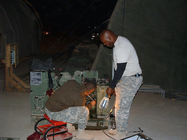 U.S. Army SGT Carlos DeFreitas (left), and SGT. James Cyrus, both assigned to Headquarter and Service Company, 449th Aviation Support Battalion, Texas Army National Guard, work late to finish repairs on a generator at Logistic Support Area, Anaconda, Balad Air Base, Iraq, on Nov. 22, 2006, during Operation Iraqi Freedom. (A3606) (U.S. Army PHOTO by STAFF SGT. Jonathan Chapman) (Released)