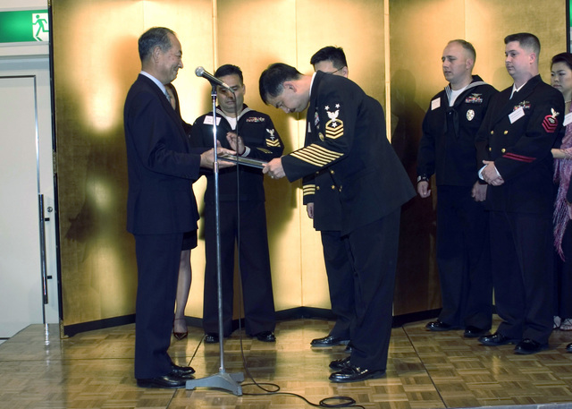 U.S. Navy Friendship Association President and Retired Japan Maritime Self Defense Force (JMSDF) Vice Adm. Makoto Yamamoto (left), presents U.S. Navy Command MASTER CHIEF Marcos F. Sibal, assigned to Fleet Activities Sasebo, Japan, with a plaque for his accomplishments and friendship with the Japanese community and the JMSDF, during an awards ceremony held at the Trinity Hotel in Yokosuka, Japan, on Nov. 22, 2006. MASTER CHIEF PETTY Officer Marcos was honored along with three other U.S. Sailor and four JMSDF Sailors. (U.S. Navy PHOTO by Mass Communication SPECIALIST 1ST Class Paul J. Phelps) (Released)