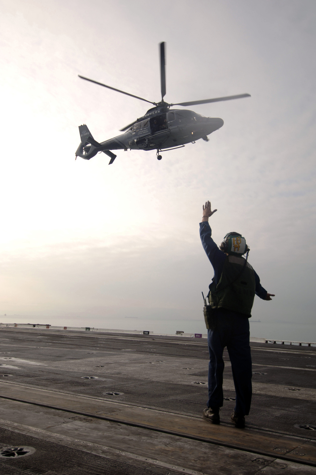 U.S. Navy AIRMAN Jeremy Donley directs a Hong Kong Government Flying Service-owned EC155B1 multi-purpose helicopter as it prepares to land on the flight deck aboard the Kitty Hawk Class Aircraft Carrier USS KITTY HAWK (CV 63) on Nov. 23, 2006, while the KITTY HAWK, and embarked Carrier Air Wing 5 (CVW-5), enter Victoria Harbor for a scheduled port call to Hong Kong (Hong Kong Special Administrative Region), People's Republic of China. (U.S. Navy photo by Mass Communication SPECIALIST SEAMAN Jimmy C. Pan) (Released)