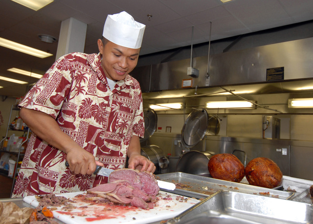 U.S. Navy Culinary SPECIALIST 3rd Class Aristotle Rivera from the Silver Dolphin Bistro galley at Naval Station Pearl Harbor, Hawaii, slices a beef brisket for Thanksgiving dinner at the galley, on Nov. 23, 2006. (U.S. Navy PHOTO by Mass Communication SPECIALIST 1ST Class James E. Foehl) (Released)