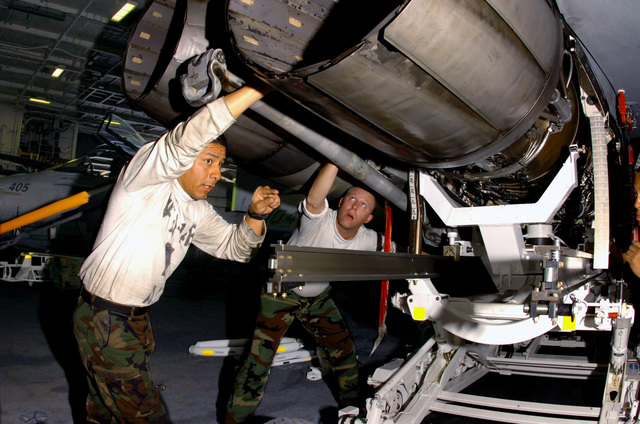 U.S. Navy Aviation Machinist's Mate 2nd Class Luis Venturasampen, (foreground), and Aviation Structural Mechanic 1ST Class Travis Andrews hoist a jet engine into place during maintenance repair onboard the Nimitz Class Aircraft Carrier USS DWIGHT D. EISENHOWER (CVN 69) on Nov. 25, 2006. EISENHOWER and embarked Carrier Air Wing 7 are currently deployed in support of maritime security operations in the Arabian Sea. (U.S. Navy photo by Mass Communication SPECIALIST SEAMAN David Danals) (Released)